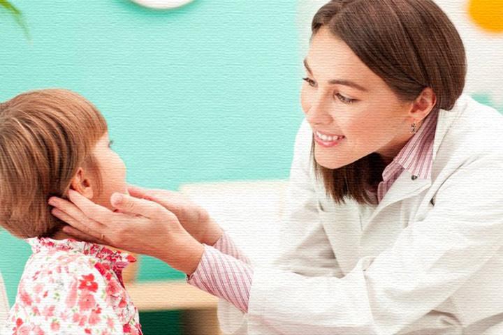 Доктор делает ребенку логопедический массаж