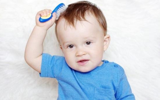 Годовалый ребенок расчесывает волосы