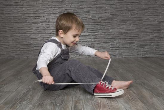 Четырехлетний мальчик завязывает шнурки