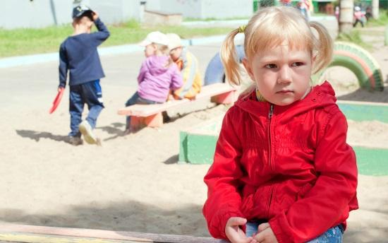 Девочка сидит в стороне от других